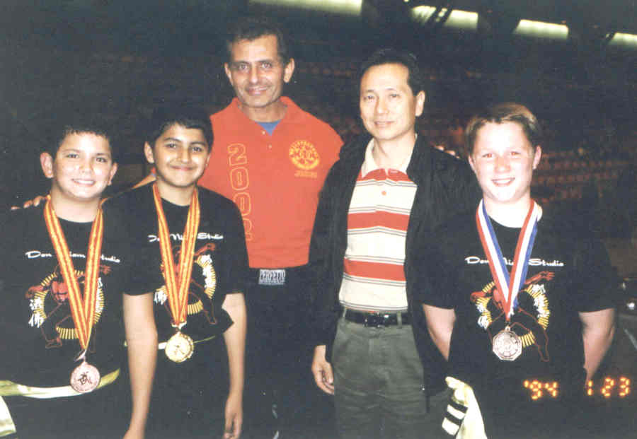 kung fu students standing with teacher with medals around their neck